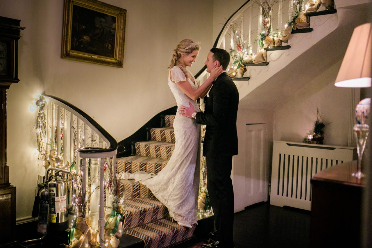 bride and groom at the bottom of the stairs holding each other