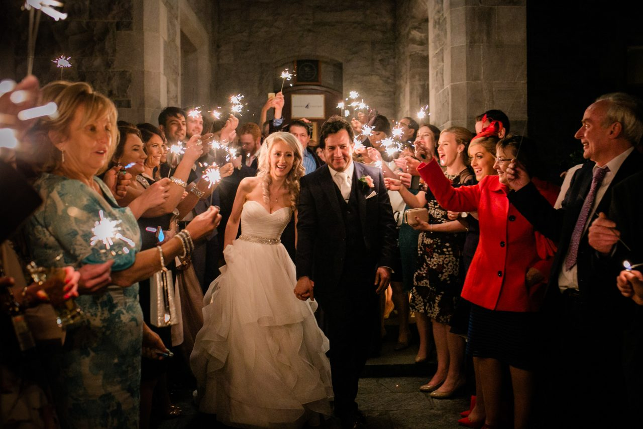 Bride and groom at night under sparklers with guests