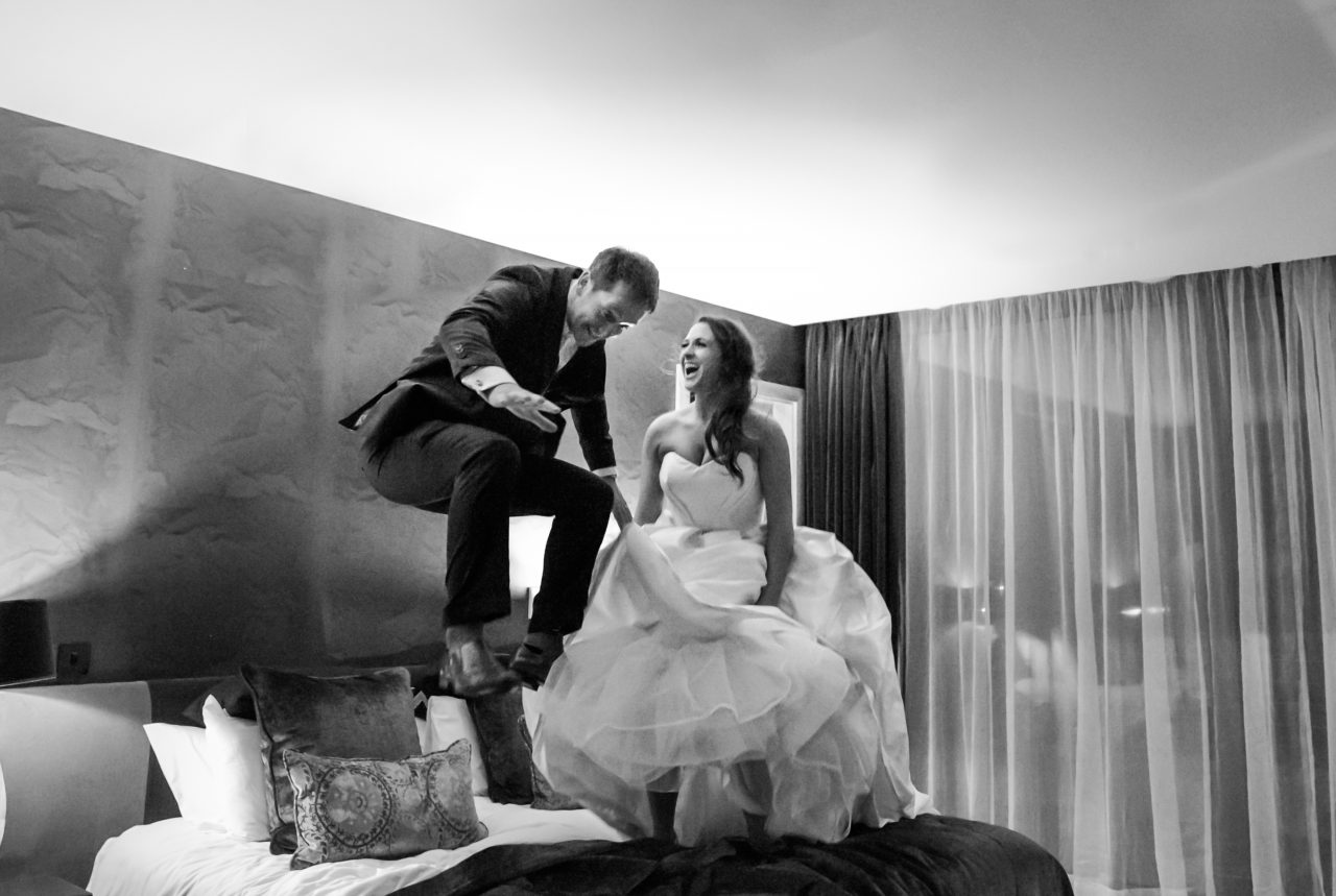 Bride and groom jumping on a bed