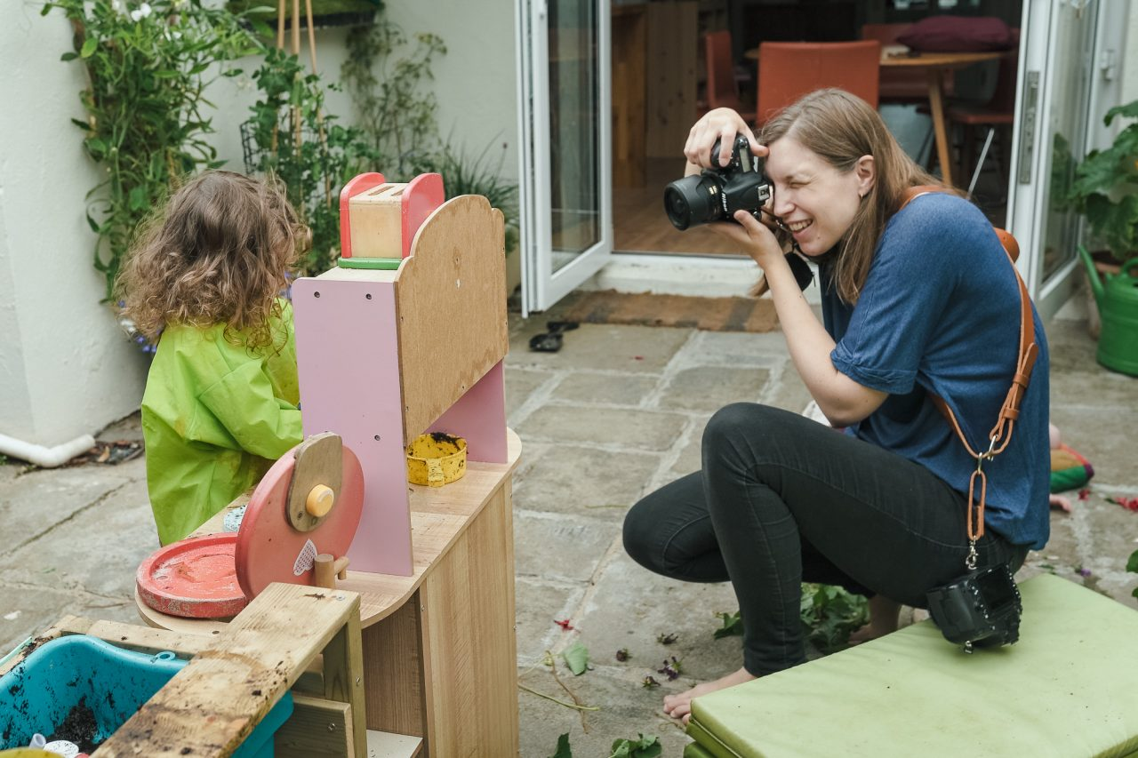 female photographer photographing a little girl playing on the patio of a house