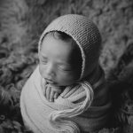 black and white photo of a newborn baby, wrapped in wool blanket and in a potato stack pose