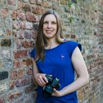 female photographer with blue top leaning against a brick wall with a camera in her hands