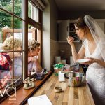 award-winning image of a bride to be eating some cake inside a kitchen while talking to older relatives who are sticking thier heads through a window from outside