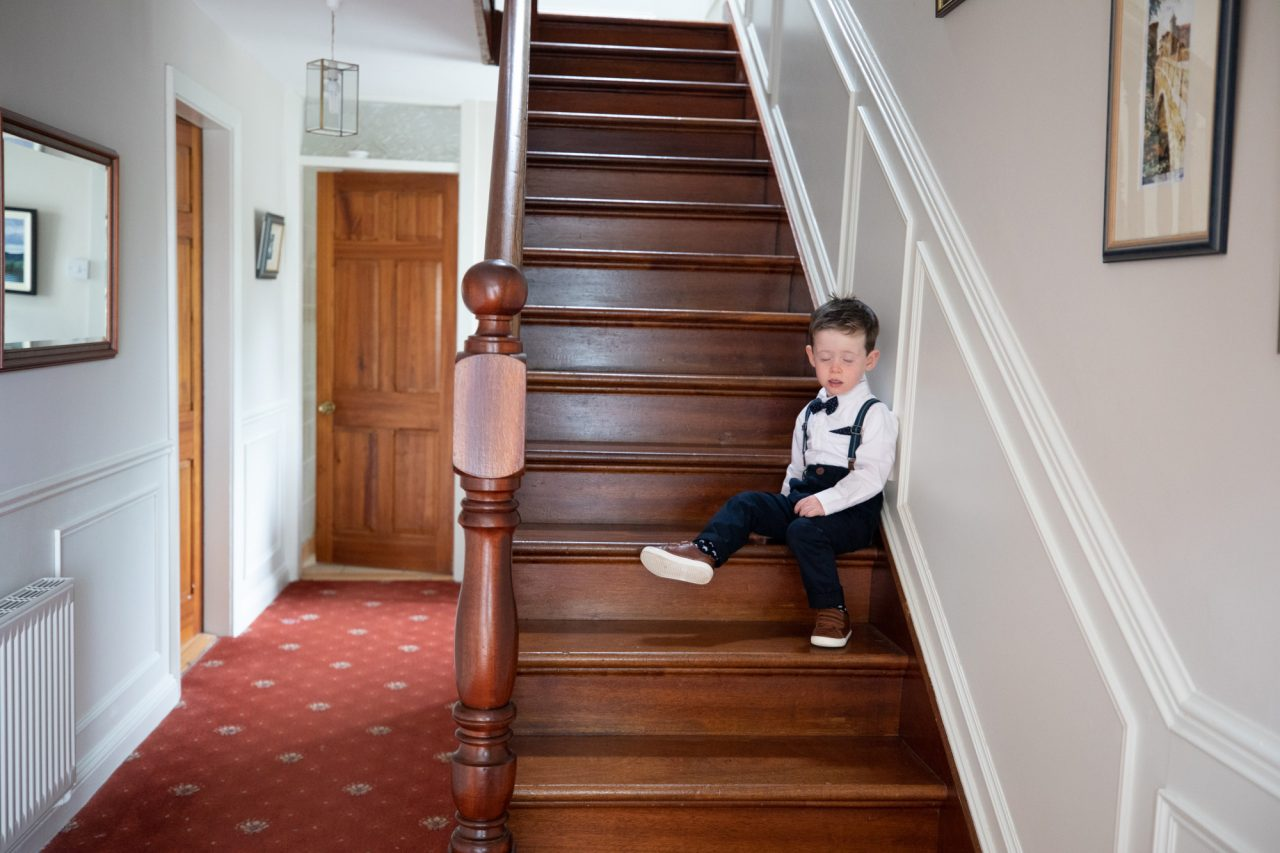 small boy wearing a shirt and dickie bow, sitting on a wooden stair case in a house