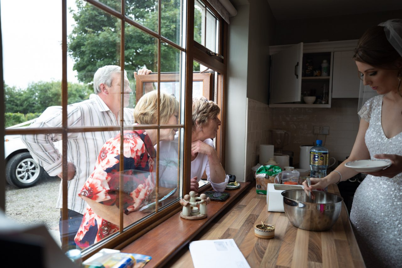 elderly people looking in through a window at a bride