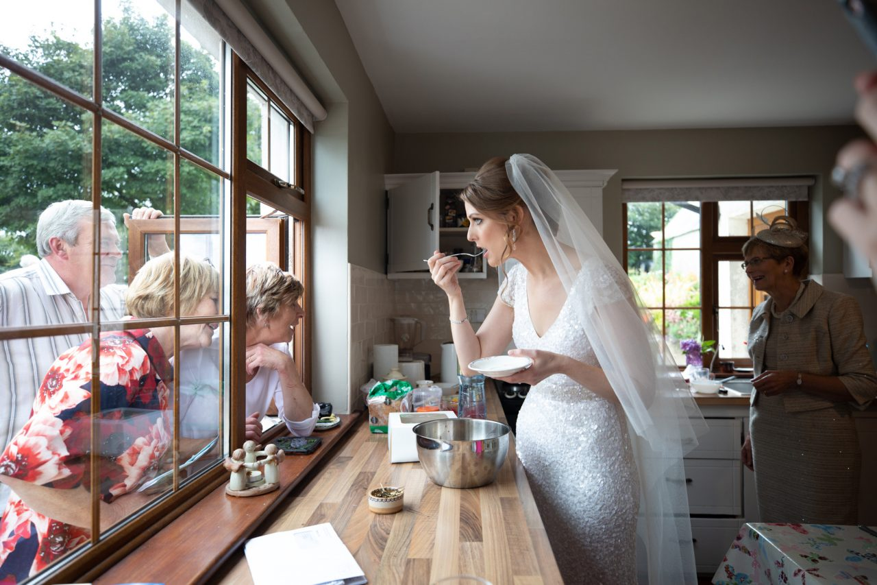 bride eating cake in a kitchen. Other people are at the edges of the fram