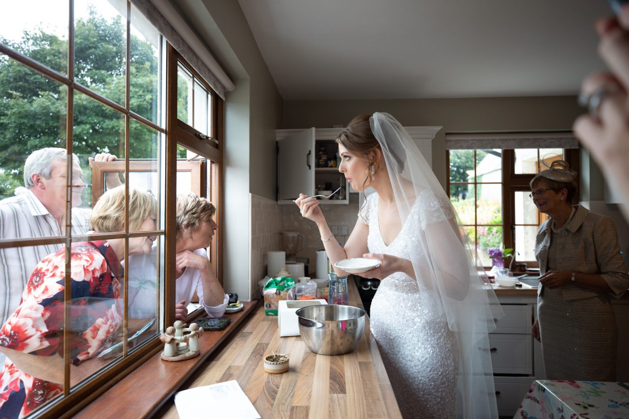 Bride eating cake with the fork in her closed mouth